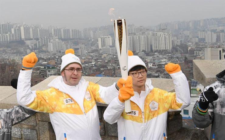 Jon Dunbar, left, carries the Olympics torch with high school student Lim Su-min through a mountain trail in Seoul, Sunday. / Korea Times photo by Seo Jae-hoon