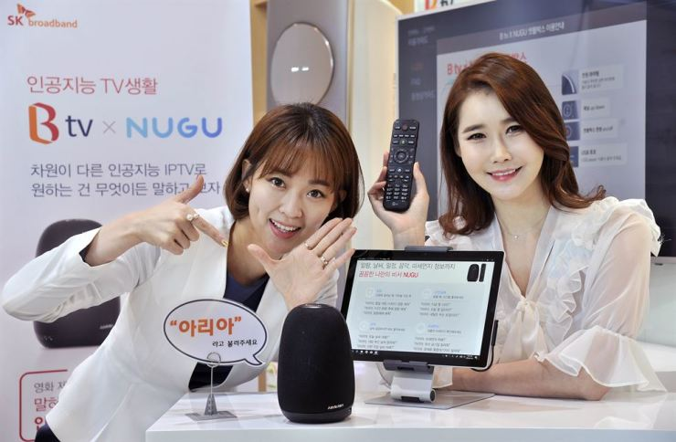 Models show SK Broadband's voice-activated artificial intelligence internet protocol TV set-top box, B tv x NUGU, and its remote control during an event to mark the launch of a new service at the company's head office in Seoul, Thursday. / Courtesy of SK Broadband