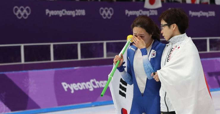 Japanese skater Kodaira Nao, left, consoles Lee Sang-hwa, two-time Olympic gold medalist, after Lee finished second in the women's 500-meter speed skating race at the Gangneung Oval. / Yonhap