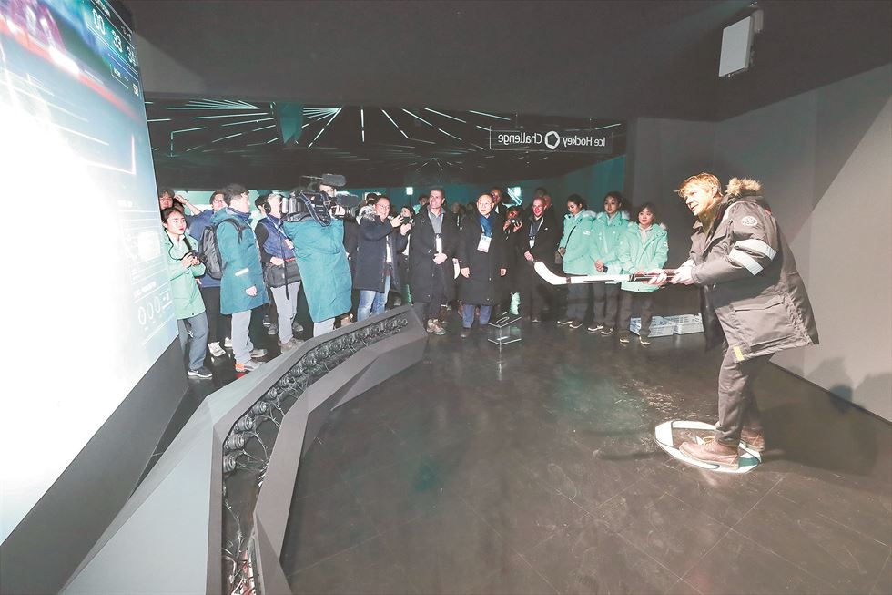Visitors experience KT's omni-point view service using the firm's 5G devices at the cross-country skiing area of the PyeongChang Winter Olympics, Feb. 11. The service allows viewers to catch up with athletes' location and performance in real time. / Yonhap