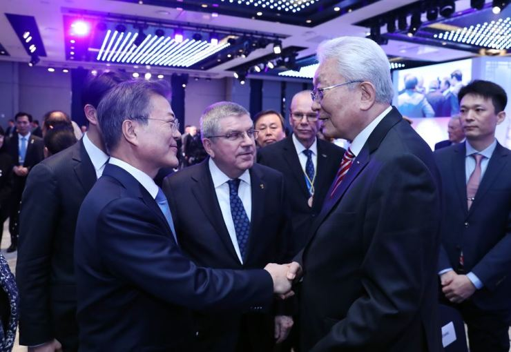 President Moon Jae-in, left, shakes hands with North Korea's International Olympic Committee (IOC) member Jang Ung at the IOC meeting in Gangneung, Monday night. Seen between the two is IOC President Thomas Bach. / Yonhap
