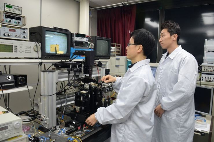 Kim Jin-tae, left, and Choi Hong-kyw, researchers of the Electronics and Telecommunications Research Institute, test a graphene-based optical modulator device that imitates neurons. / Courtesy of Electronics and Telecommunications Research Institute