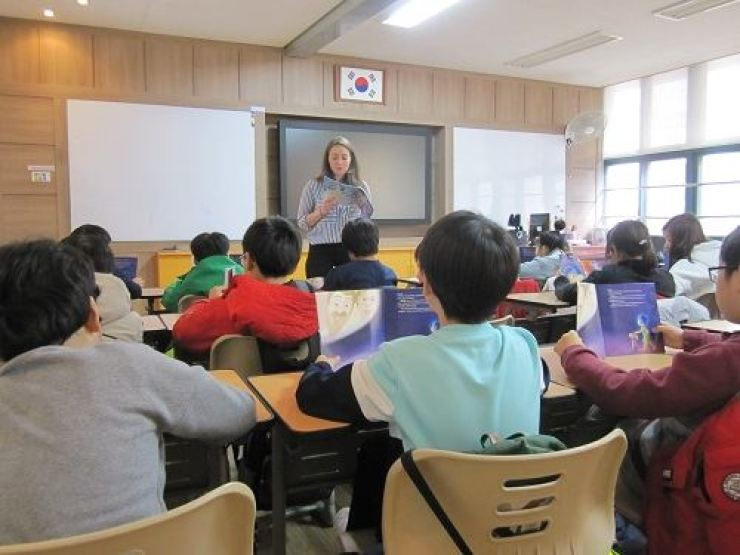 A native English-speaking teacher reads with students at a Jung-gu, Seoul, school in this photo from the Hankang Times home page.