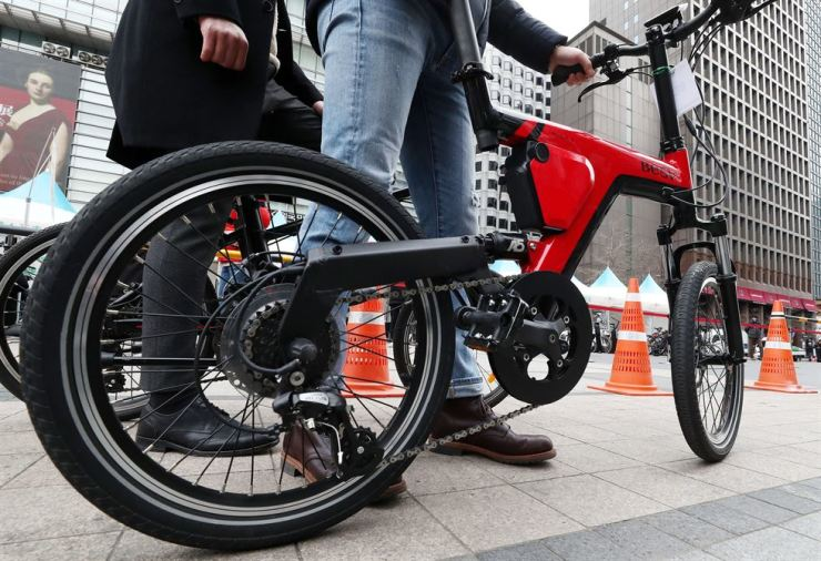 People test an electric bicycle at Cheonggyecheon Stream in Jongno-gu, Seoul, on Mar. 21, where the Ministry of the Interior and Safety prepared a test zone. / Yonhap