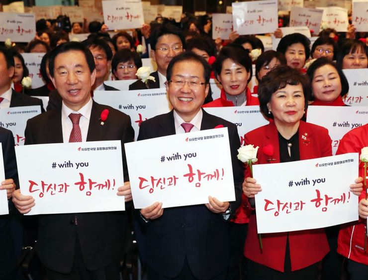 Liberty Korea Party Chairman Hong Joon-pyo, center, and floor leader Kim Sung-tae, left, hold signs supporting the #MeToo movement, along with female party members, March 6. / Yonhap
