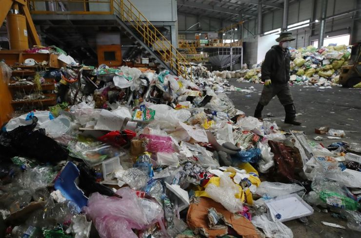 A man walks by a big pile of collected waste at a trash center in Chuncheon, Gangwon Province, Tuesday. / Yonhap