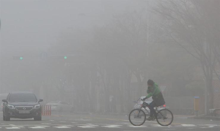 A bike rider crosses a road amid dense fine dust in Gwangju, Monday. / Yonhap
