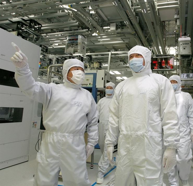 SK Group Chairman Chey Tae-won, in the foreground, right, is briefed about details of chip-producing equipment installed at the M11-dubbed manufacturing facility operated and managed by the group's semiconductor affiliate, SK hynix // file photo Korea Times