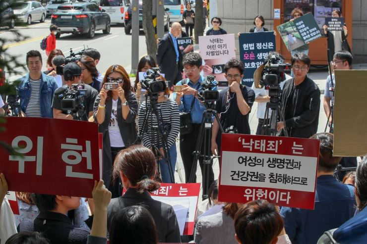 Civic groups rally in front of the Constitutional Court ahead of a public petition on the constitutionality of the current abortion law. Protesters on one side claim the law is unconstitutional (front) while those on the other side support the ban. / Yonhap