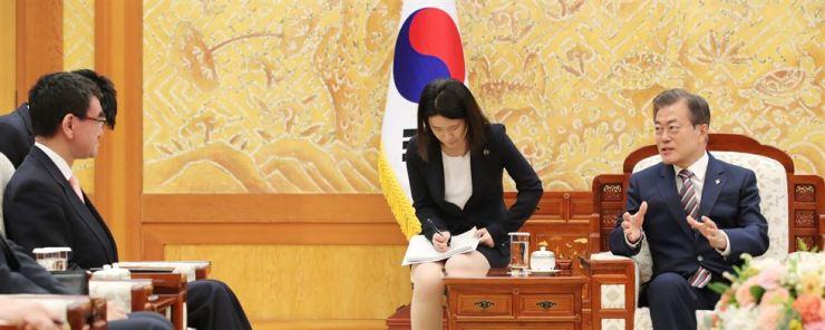 South Korean President Moon Jae-in, right, talks to Japanese Foreign Minister Taro Kono at Cheong Wa Dae, Thursday. Yonhap