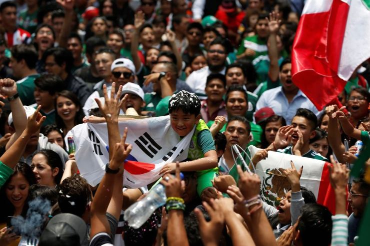 Mexican soccer fans celebrate with a young South Korean citizen in Mexico City, Mexico, June 27. REUTERS-Yonhap
