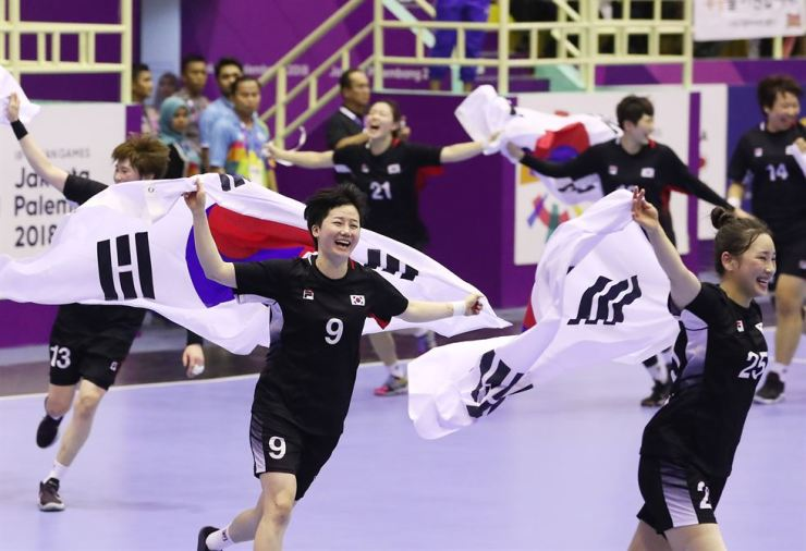 South Korean handball players celebrate winning a gold medal after defeating China in the women's handball final at the POPKI Sport Hall in Jakarta, Indonesia, Thursday. / Yonhap