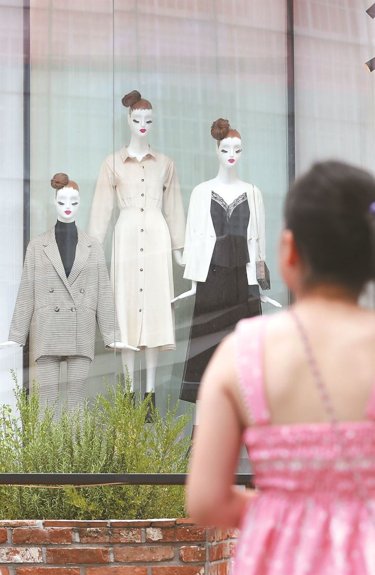 A child in a summer dress stares at mannequins dressed in fall attire at a shop in Myeong-dong, Seoul, Sunday, when temperatures peaked at 36 degrees Celsius in the capital. The heat wave is forecast to continue, with Typhoon Yagi and Typhoon Leepi unlikely to affect or cool the Korean Peninsula. Yonhap