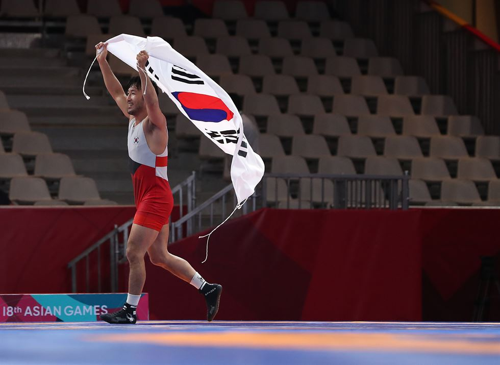 South Korean Greco-Roman wrestler Ryu Han-su bites his gold medal from the men's 67kg category at the 18th Asian Games at Jakarta Convention Center Assembly Hall in Jakarta, Tuesday. / Yonhap