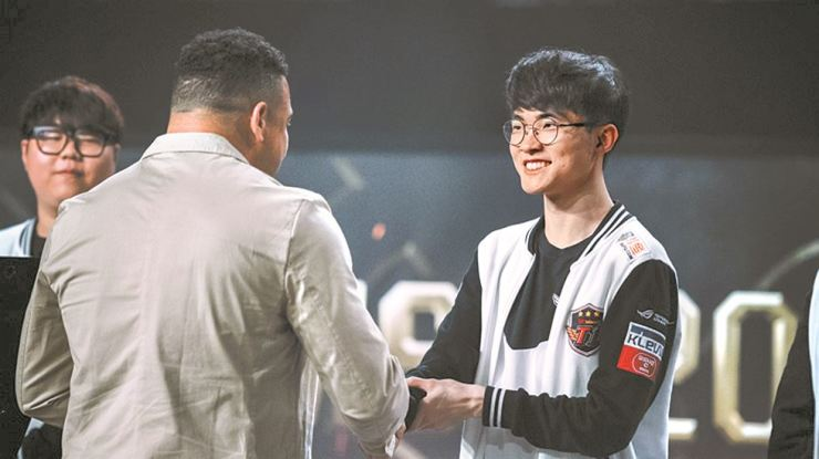 Brazilian football legend Ronaldo, left, shakes hand with Lee Sang-hyeok, a member of SK Telecom T1, during an award ceremony after the Korean team won the online game League of Legends' Mid-Season Invitational event at the Jeunesse Arena in Rio de Janeiro, on May. 23, 2017. / Courtesy of Riot Games