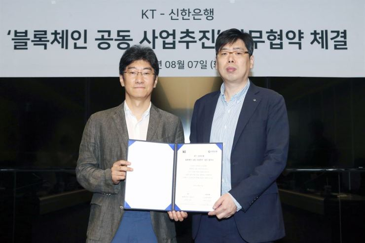 Shinhan Bank Digital Strategy Department head Jang Hyeon-ki, right, stands with KT Platform Service director Kim Hak-joon during a signing ceremony at the KT head office in central Seoul, Tuesday. / Courtesy of Shinhan Bank