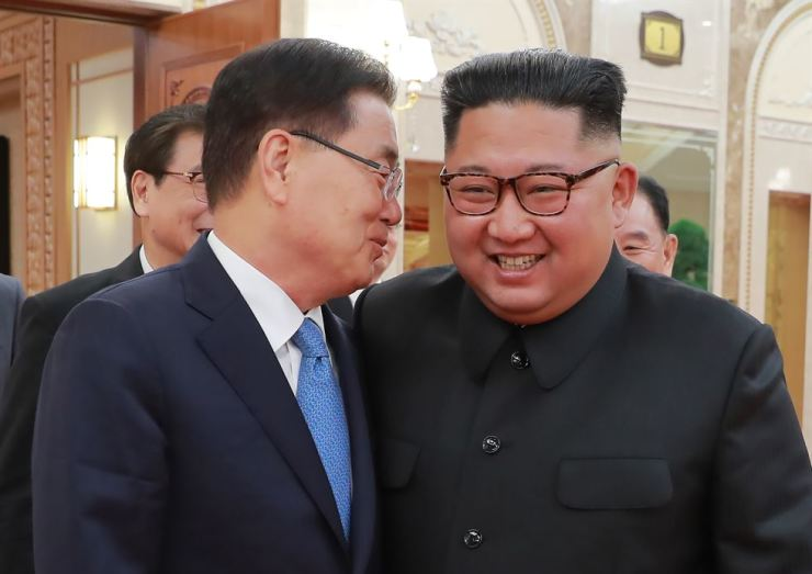 President Moon Jae-in's special envoy and National Security Office chief Chung Eui-yong, left, whispers to North Korean leader Kim Jong-un. Courtesy of Cheong Wa Dae