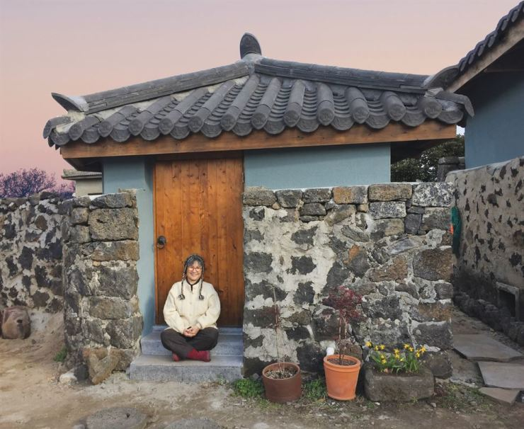 Brenda Paik Sunoo sits in front of her renovated stone house in the Jeju Island village of Aewol. / Courtesy of Brenda Paik Sunoo