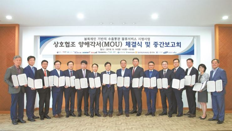 Kim Hyung-tae, ninth from left, who leads the logistics business unit of Samsung SDS, poses for a photo with other executives and officials of government offices and companies related to exports, after signing an MOU at Seoul Main Customs, Friday, pushing for a Korea Customs Service-led project to establish a blockchain-based export customs clearance system. / Courtesy of Samsung SDS