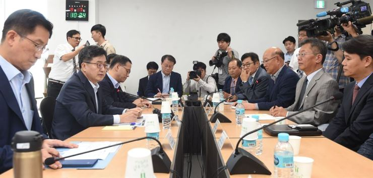 Finance Minister Kim Dong-yeon, second from left, discusses ways to develop a hydrogen ecosystem with a group of industry executives at the head office of Elchemtech, a producer of hydrogen energy generation equipment, in Seoul, Friday. Courtesy of the Ministry of Economy and Finance
