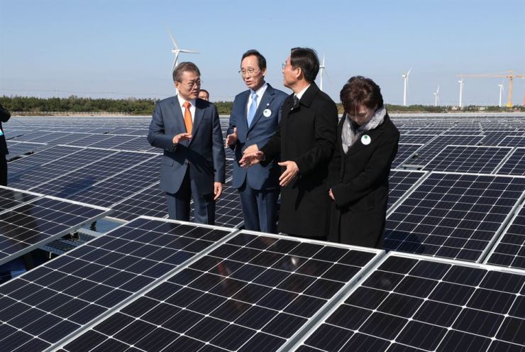President Moon Jae-in talks with ministers and the North Jeolla Province governor at a solar energy plant in Gunsan in the province, Tuesday. From left are Moon, Governor Song Ha-jin, Trade, Industry and Energy Minister Sung Yun-mo and Land, Infrastructure and Transport Minister Kim Hyun-mee. / Yonhap