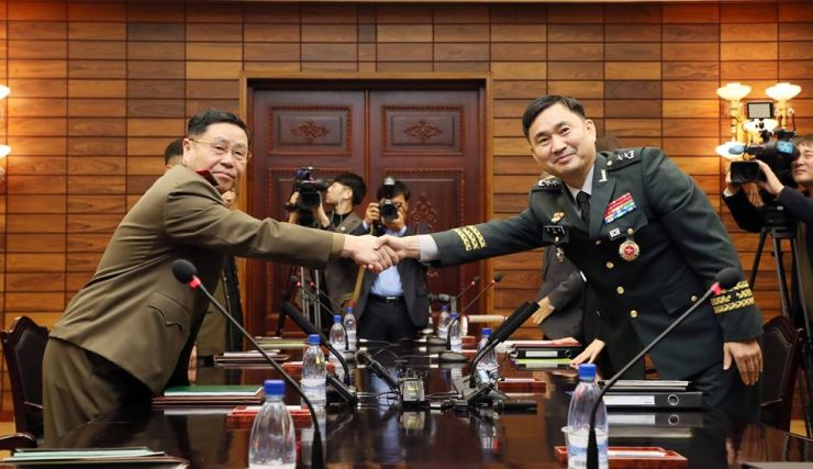 Major Gen. Kim Do-gyun of South Korea, right, and his North Korean counterpart Lt. Gen. An Ik-san shake hands ahead of a general-level military meeting at Tongilgak, the North's side of the truce village of Panmunjeom inside the Demilitarized Zone (DMZ), Friday. / Joint Press Corps