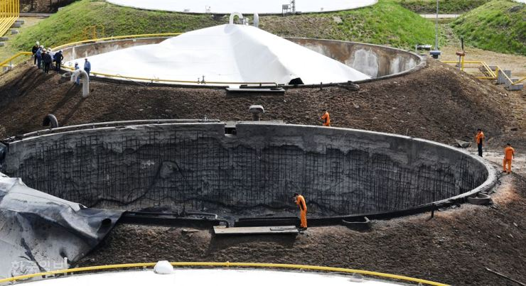 Inspectors look around a charred oil storage tank in Goyang, Gyeonggi Province, Monday. /Korea Times photo by Hong In-ki