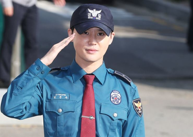 Kim Jun-su, a member of boy band JYJ, salutes fans after he is formally discharged after serving the country's mandatory military duty in Suwon, just south of Seoul, Monday. The singer fulfilled the duty as a policeman at a regional police agency.