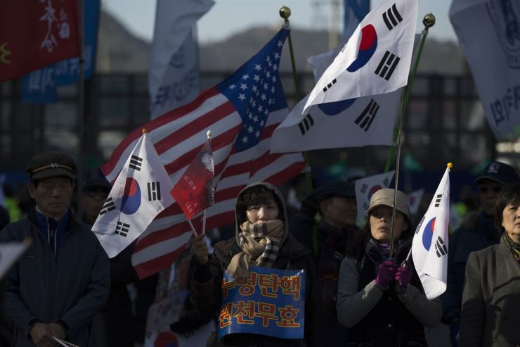 Rally participants seeking the cancelation of the impeachment of President Park Geun-hye wave South Korean and U.S. flags in central Seoul on March 9, 2017, one day before the impeachment decision. Korea Times photo by Choi Won-suk
