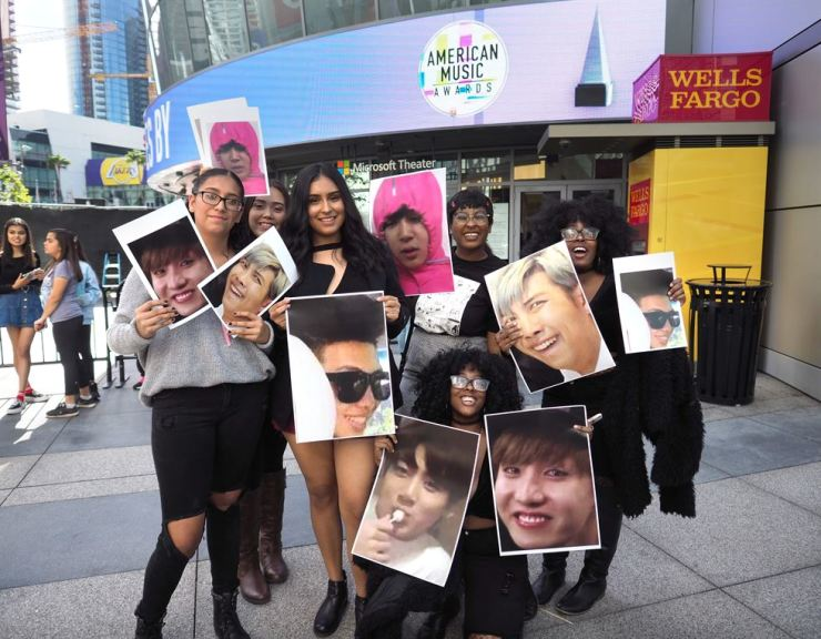 BTS fans, better known among themselves as ARMY, hold photos of their favorite BTS members in front of Microsoft Theater in Los Angeles last year for the American Music Awards. Some overseas fans of the superstar K-pop band donated for Korean survivors of wartime sexual slavery. AFP-Yonhap