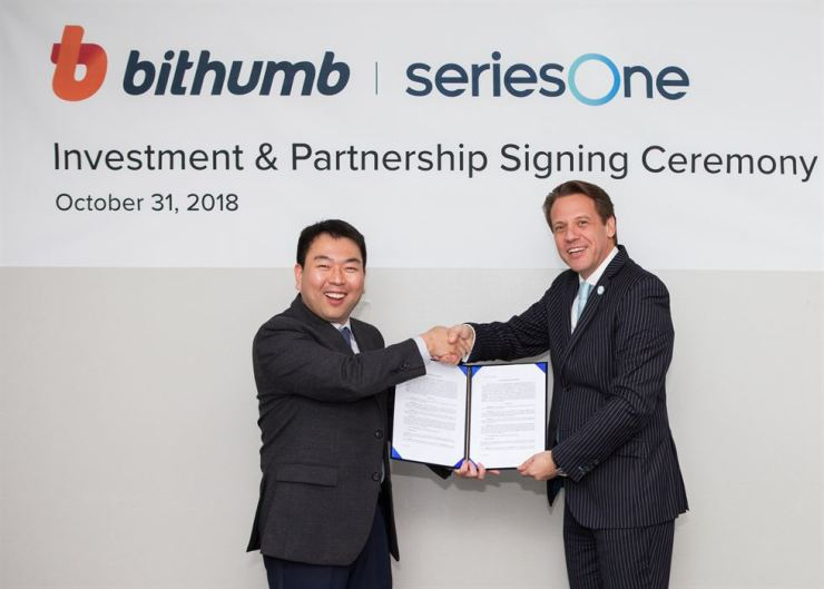 Bithumb CEO Heo Back-young, left, shakes hands with SeriesOne CEO Michael Mildenberger during an investment and partnership signing ceremony at the crypto exchange's head office in Seoul, Oct. 31. Courtesy of Bithumb