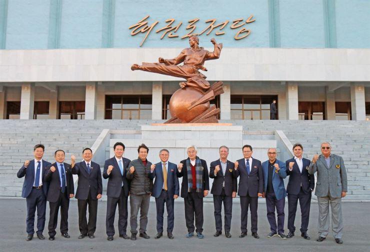 World Taekwondo President Choue Chung-won, sixth from right, and International Taekwondo Federation President Ri Yong-sun, sixth from left, with other dignitaries in front of the Taekwondo Hall in Pyongyang, Thursday.