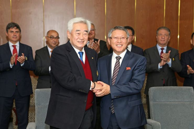 Choue and Ri shake hands during the signing ceremony in Pyongyang, Friday.