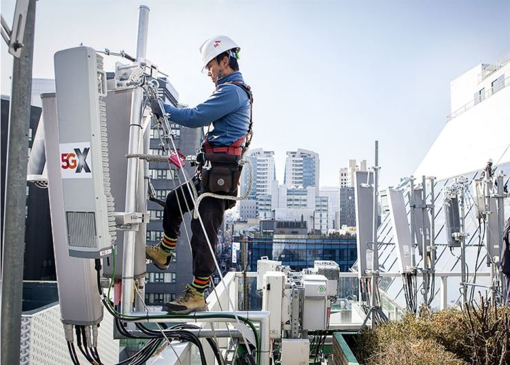 An SK Telecom engineer tests one of the firm's 5G base stations on the rooftop of a building in Myeong-dong, central Seoul, Wednesday. / Courtesy of SK Telecom