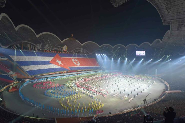 The mass gymnastics performance on Monday features the flags of Cuba (left) and North Korea. Yonhap-Rodong Sinmun