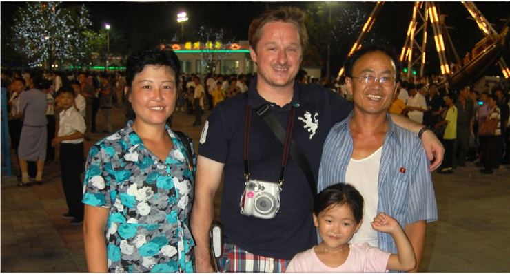 Michael Spavor poses with a North Korean family that approached him for a picture at Pyongyang's Kaeson Night Fun Fair, August 2010. / Courtesy of Jon Dunbar