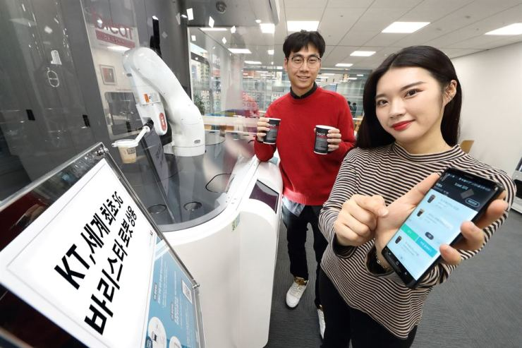 Models pose at an unmanned cafe featuring a 5G network technology-based barista robot in southern Seoul, in this photo provided by KT, Tuesday. / Courtesy of KT