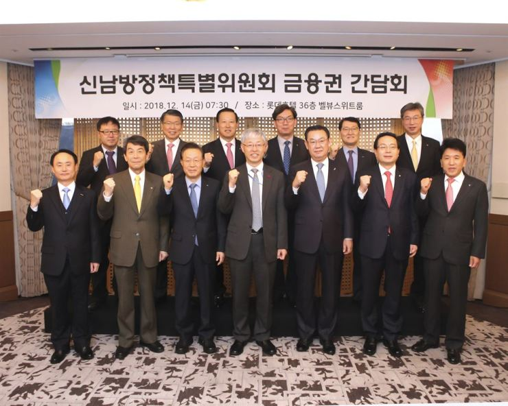 Kim Hyun-chul, center, a Presidential economic adviser, center, raises his fist with chief executives of banks ahead of their meeting in Seoul, Friday to discuss expansion in Southeast Asia. Courtesy of Korea Federation of Banks