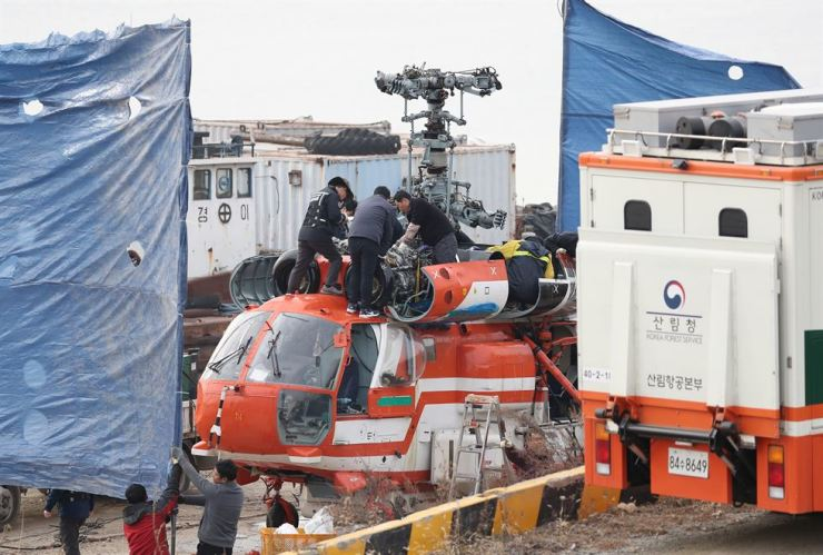 Mechanics dismantle the KFS helicopter in Guri, Gyeonggi Province Sunday, and the parts will be sent to the Aviation and Railway Accident Investigation Board for a thorough analysis. The KFS helicopter crashed into the Han River Saturday, which killed one and injured two others on board. Yonhap