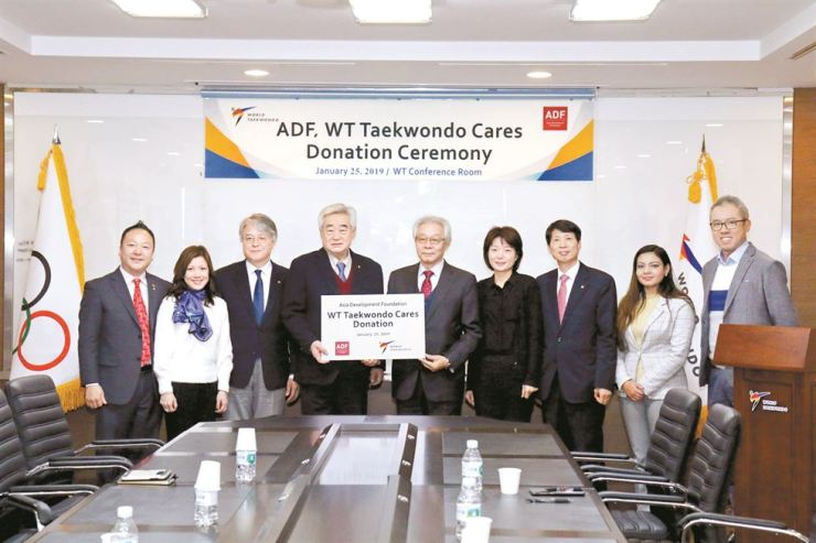 World Taekwondo (WT) President Choue Chung-won, fourth from left, poses with Cho Nam-chul, fifth from left, executive director of the Asia Development Foundation during a donation ceremony at the WT headquarters in Seoul, Friday. Courtesy of WT