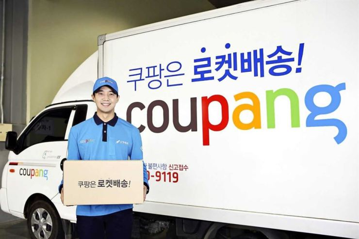 A Coupang employee poses with a delivery truck in this photo provided by the firm Tuesday. The e-commerce firm said it has delivered more than 1.7 million items a day through its Rocket Delivery free-next-day delivery service. / Courtesy of Coupang