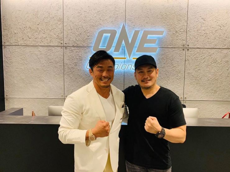 ONE Championship Chairman Chatri Sityodtong, right, puts his arms around Korean-Japanese mixed martial artist Yoshihiro Akiyama, who is better known as Choo Sung-hoon in Korea, at ONE Championship headquarters in Singapore in this November 2018 file photo. / Courtesy of ONE Championship