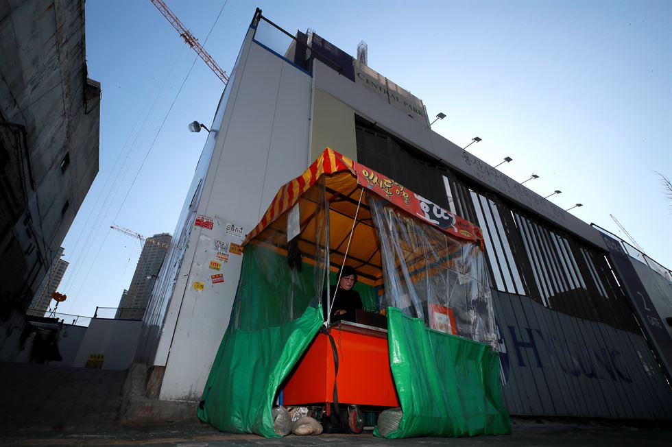 A temporary structure built on a building in Yongsan to protest a redevelopment plan for the area is on fire after police raided the site early Jan. 20, 2009. / Korea Times file