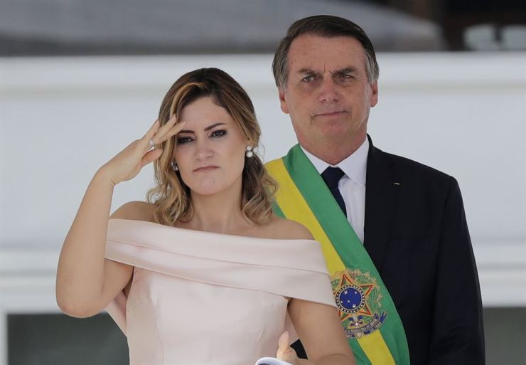 With her husband, Brazil's new President Jair Bolsonaro in the background, Brazil's new first lady Michelle Bolsonaro gives a military salute from the Planalto Presidential palace, in Brasilia, Brazil, Tuesday, Jan. 1, 2019. AP-Yonhap