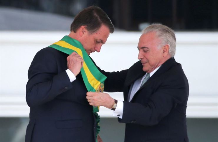 Brazil's new President Jair Bolsonaro, left, receives the presidential sash from outgoing President Michel Temer at the Planalto Palace, in Brasilia, Brazil January 1, 2019. REUTERS-Yonhap