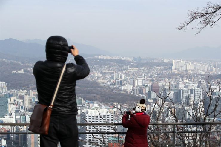 Unnamed tourists on Mount Nam take pictures for scenic views of downtown Seoul, Tuesday. Yonhap