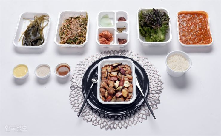 A pork meal comes in 10 plastic containers when ordered via a food delivery app. The Ministry of Environment plans to survey the use of plastic and other disposable containers in food delivery services in an effort to reduce the use of plastic. / Korea Times file