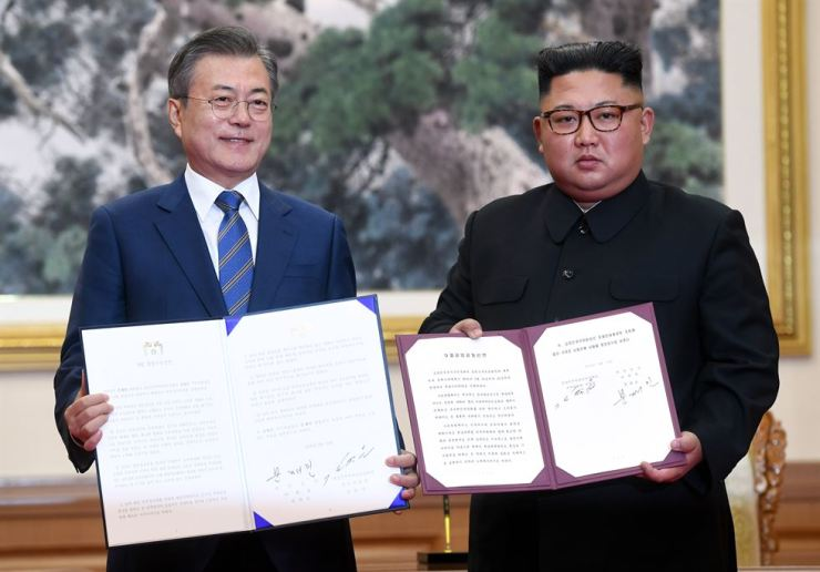 In this Sept. 19, 2018 photo, South Korean President Moon Jae-in, left, and North Korean leader Kim Jong-un hold the documents after signing at the Paekhwawon State Guesthouse in Pyongyang, North Korea. AP-Yonhap