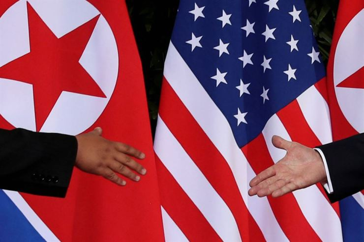 U.S. President Donald Trump and North Korea's leader Kim Jong-un meet at the start of their summit at the Capella Hotel on the resort island of Sentosa, Singapore, June 12, 2018. The United States and North Korea are considering an exchange of liaison officers. Reuters