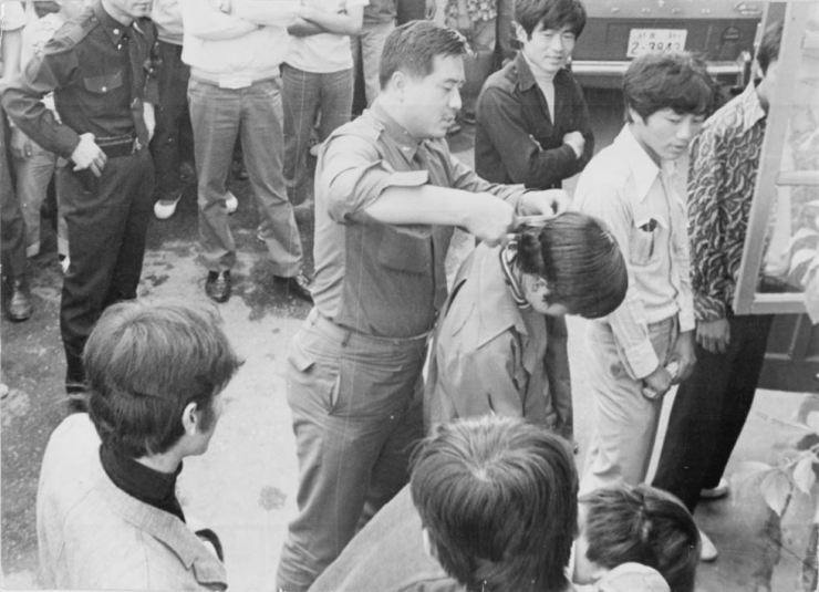 A man wearing military uniform cuts a young man's hair in front of others in this undated Korea Times file photo. In 1973, the Park Chung-hee government adopted the Minor Offenses Act banning men from having long hair and women wearing skirts shorter than 17 centimeters above the knee. / Korea Times file
